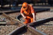 Ein Bauarbeiter macht an einem Gleis Reparaturen. (Bild: Keystone / Martin Ruetschi)
