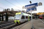 Ausfahrt des neuen Niederflurtriebzugs aus dem Bahnhof Wolhusen (linkes Bild). Zuvor nahm Lokführer Philipp Heil (links) die Geschenke von Josef Auchli, Leiter der Arbeitsgruppe Verkehr, entgegen. (Bilder Roger Grütter)