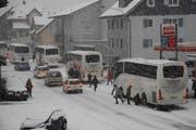 Stau vergangenes Wochenende in Wolfenschiessen: Die Cars werden mit Schneeketten wintertauglich gemacht. (Bild: Franz Hess / Neue NZ)
