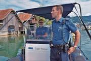 Die Polizisten Pfister (vorn) und Wettach lassen ihren Blick über das Geschehen im Zuger Hafen schweifen. (Bild: Raphael Biermayr (16. Juli 2017))