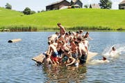 Teilnehmer des Pfarreilagers Kägiswil bringen das Floss in Wildhaus zum Sinken. (Bild: zvg)