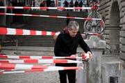 Shahram Entebhabi (48) deckt den Luzerner Rathaussteg mit rotweissem Absperrband ein. (Bild: FelderVogel)