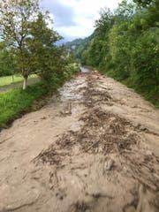 Bei der «gedeckten Brücke» in Giswil fliesst eine Masse aus Wasser, Schlamm, Holz und Steinen die Laui hinunter. (Bild: Leserbild)