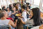 Auf dem Weg zurück von der Rigi nach Vitznau gibt es für diese chinesischen Touristen in der Zahnradbahn noch eine Portion Pommes frites mit Ketchup und Bratwurst. (Bild Roger Grütter)