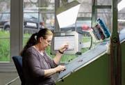 Eine Mitarbeiterin der Lantal Textiles AG prüft einen produzierten Teppich auf Fehler. (Bild: Peter Klaunzer/Keystone (Melchnau, 12. April 2012))