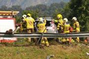 Rettungskräfte bemühen um die Insassen eines am Unfall beteiligten Fahrzeuges. (Bild: Robert Hess / Neue OZ)