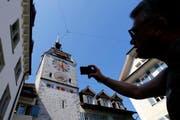 Ein Tourist auf Besuch in der Stadt Zug schiesst ein Foto vom Zuger Zytturm. (Bild: Stefan Kaiser/Neue ZZ)