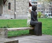 Andächtig sitzt Andreas Hofers Engel auf der Parkbank, den Rücken zur Kirche gekehrt. (Bild: Andreas Faessler (Zug, 11. April 2017))
