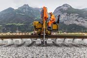 Ein Arbeiter verlegt auf der Neat-Strecke bei Erstfeld Schienen. Bild: Gaëtan Bally/Keystone (20. August 2014)