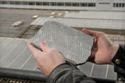 Ein Bruchstück einer der Eternitplatten, die vom Bahnhofdach fielen. Im Hintergrund sieht man Stapel der Platten auf dem Dach. (Bild Pius Amrein/Neue LZ)