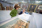 Stadtarchivarin Daniela Walker (links) und die für die städtische Kunstsammlung zuständige Doris Bucher im Archivraum mit den Gemälden. (Bild Pius Amrein)