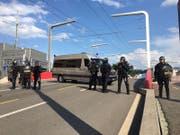 Die Polizei steht parat: Mit Gewehr und Schlagstock bewaffnet. (Bild: kük)