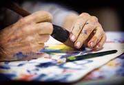Eine ältere Frau in einem Malkurs speziell für demente Menschen. (Bild: Getty)