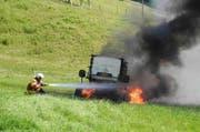Die Feuerwehr beim Löschen der brennenden Heuballenpresse. (Bild: Kapo Schwyz)
