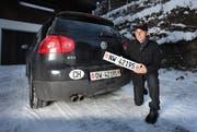 Viktor Röthlin mit der neuen Autonummer NW 42195 vor dem Firmenauto mit der Autonummer OW 42195, aufgenommen bei sich zu Hause in Ennetmoos. (Bild: Roger Zbinden/Neue LZ)
