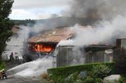 Die Feuerwehr verhindert, dass das Feuer auf weitere Gebäude übergreift. (Bild: Kantonspolizei Schwyz)