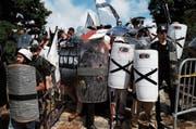 Rechtsextreme verbarrikadieren sich hinter Schutzschildern mit ihrem Symbol: schwarzes Kreuz auf weissem Grund. (Bild: Joshua Roberts/Reuters (Charlottesville, 12. August 2017))