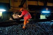 Ein Mitarbeiter einer Gleisbaufirma bedient eine Maschine. (Bild Dominik Wunderli)