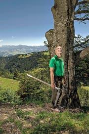 Revierförster Hans Ming (58) steht mit seiner Messkluppe vor einer Buche im Gebiet Oberänzi. Im Hintergrund die Pilatuskette. (Bild Nadia Schärli)