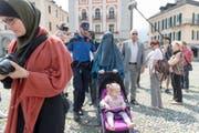 1. Juli: Im Tessin tritt das Burkaverbot in Kraft. Ab jetzt ist es verboten, in der Öffentlichkeit das Gesicht zu verhüllen. Andernfalls drohen Bussen zwischen 100 und 1000 Franken. In Locarno ermahnt die Polizei Nora Illi, Frauenbeauftragte des Islamischen Zentralrats der Schweiz IZRS, ihr Gesicht nicht zu verhüllen (unser Bild). (Bild: Keystone)