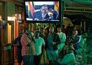Enttäuschte Blicke in einer Bar während der Rede von Simbabwes Präsident Robert Mugabe. (Bild:)