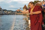 Lama Tsewang Nyima übergibt das Mandala der Reuss. Zahlreiche Besucher hatten zuvor die Entstehung des tibetischen Kunstwerkes verfolgt. (Bild: Keystone)