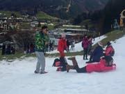 Statt auf den Titlis in den Kunstschnee: Touristen vergnügen sich oberhalb der Talstation in Engelberg. (Bild: René Meier)