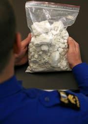 Ein Beamter der Luzerner Polizei hält einen Sack mit einem Kilo Kokain. (Bild: Archiv LZ)