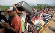Venezolaner stehen auf der Grenzbrücke «Simon Bolivar» Schlange, um nach Kolumbien zu gelangen. (Bild: Fernando Vergara/AP (21. Februar 2018))
