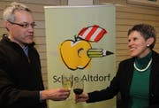 Schulratsvizepräsident Alexander Imhof und Schulratspräsidentin Ruth Regli stossen an, im Hintergrund das Logo. (Bild Urs Hanhart/Neue UZ)