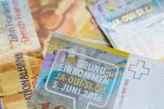 """Zehnernoten mit dem Aufkleber """"I love Grundeinkommen, Ja-Oui-Si.ch, 5. Juni 2016"""", fotografiert an der Aktion """"Für ein Bedingungsloses Grundeinkommen"""" im März in Zürich. (Bild: Keystone / Ennio Leanza)"""