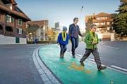 Mit der Einfärbung des Trottoirs im Udligenswiler Zentrum hat die Gemeinde den Schulweg für Kinder sicherer gemacht. Im Bild: Manuela Kohli mit Sohn Laurin (6, rechts) und dem Kindergarten-Gspänli Niklas (5). (Bild Pius Amrein)