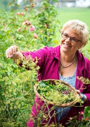Romana Zumbühl (47) sammelt Kräuter in ihrem Garten, die sie für die Erntedank-Pastete verwendet. (Bild: Dominik Wunderli / Neue LZ)