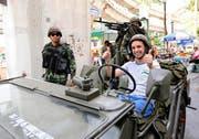 Gelöste Stimmung in Bangkok trotz Ausrufung des Kriegsrechts: Ein marokkanischer Tourist posiert für ein Erinnerungsfoto in einem Armeefahrzeug der thailändischen Armee. (Bild: Keystone)
