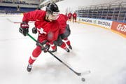 Von einem Teamkollegen bedrängt, kontrolliert Nino Niederreiter den Puck in der gestrigen Übungseinheit der Schweizer in der Trainingshalle des Eispalastes von Moskau. (Bild: Keystone/Salvatore Di Nolfi)