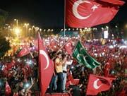 Mit Landesflaggen begehen Tausende Personen die Siegesfeiern zum Jahrestag des Putschversuches. (Bild: Tolga Bozoglu/EPA (Istanbul, 15. Juli 17))