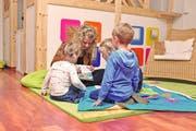 Szene in der Kindebetreuung: Eine Mitarbeiterin zeigt drei Schützlingen ein altersgerechtes Buch über den Stassenverkehr. (Bild: PD/Small Foot AG)