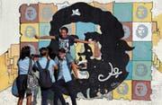 Jugendliche posieren in Havanna vor einem Wandbild von «Che» Guevara. (Bild: Alejandro Ernesto/EPA (25. Oktober 2016))