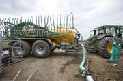 Ein Bauer pumpt Gülle um. (Symbolbild Keystone)