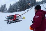 Schanzenmitarbeiter Toni Töngi schaut, wie Pistenfahrzeugfahrer Noldi Hess mit der brandneuen Windenmaschine die Landebahn präpariert. (Bild: PD)
