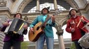 Die drei Musiker der «Musig 6020» vor dem Luzerner Torbogen auf dem Bahnhofplatz: Robert Brun (Akkordeon), Werner Richli (Gitarre und Songwriter) und Roland Huber (Schlagzeug und Gesang). (Bild: Screenshot Youtube)