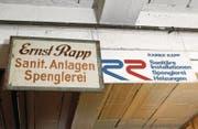 Das Firmenschild des Gründers Ernst Rapp und ein neueres an der Decke der Werkstatt. (Bild: Werner Schelbert (13. Dezember 2017))