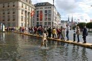Hochwasserschäden nehmen gemäss der Gebäudeversicherung Luzern zu. Im Bild ist zu sehen, wie Einwohner und Gäste in Luzern nach dem Hochwasser von 2005 über einen Steg den Schwanenplatz passieren. (Archivbild / Keystone / Sigi Tischler)
