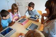 Lukas, Ladina und Christian (von links) entdecken zusammen mit Karin Mathis die Geheimnisse des iPad. (Bild: Romano Cuonz / Neue NZ)