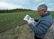 Robert Stierli schaut sich an, wo künftig ein Kiesweg über das Feld führen soll. (Bild: Stefan Kaiser (Cham, 8. November 2017))