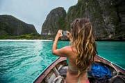 Wer solche Momente möglichst eindrücklich festhalten will, sollte über eine Digital- oder Spiegelreflexkamera nachdenken. Im Bild: Eine Frau fotografiert eine tropische Insel in Thailand. (Bild: Getty/Jordan Siemens)