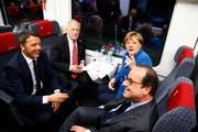 Italiens Premierminister Matteo Renzi, Bundespräsident Johann Schneider-Ammann, die deutsche Bundeskanzlerin Angela Merkel und Frankreichs Staatschef François Hollande im Eröffnungszug unterwegs von Erstfeld nach Bodio. (Bild: Keystone / Gabriele Putzu)
