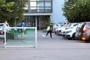Gleich wird ein Auto den Schulhausplatz verlassen, derweil die Kids weiter Fussball spielen. (Bild Charly Keiser)