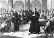Der Schweizer Reformator Ulrich Zwingli im Disput mit einem Mönch im Jahr 1523 in Zürich. (Bild: Getty)