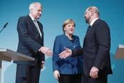Horst Seehofer, Angela Merkel und Martin Schulz (von links) bei der gemeinsamen Pressekonferenz gestern in Berlin. (Bild: Clemens Bilan/EPA)